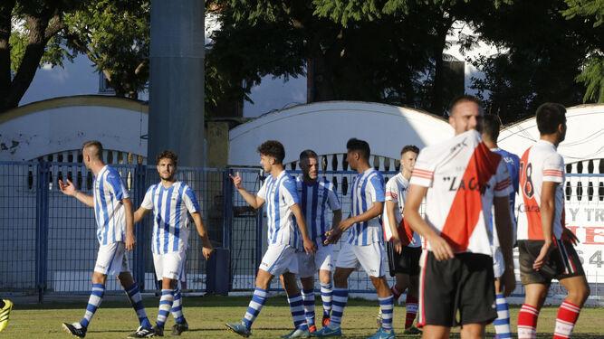Los futbolistas del Jerez Industrial celebran el 1-0 al filo del descanso mientras los jugadores sanluqueños lamentan el tanto.