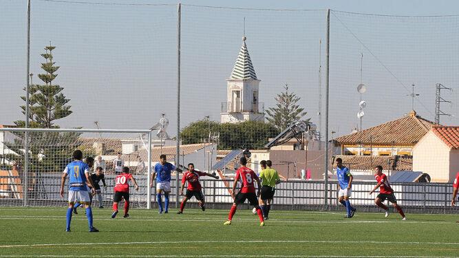 Jugada del partido del pasado domingo en el Sánchez Portella, con el campanario de la iglesia de Torrecera al fondo.