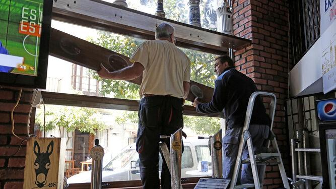 Trabajos de sustitución ayer de la cristalera del ventanal dañado en la cervecería 'El Gorila' de la plaza Plateros.
