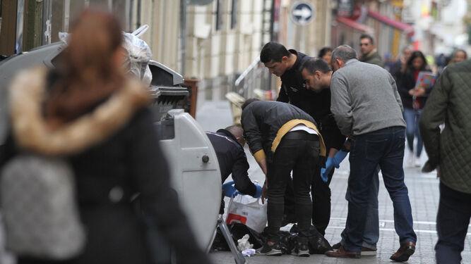 Varios agentes de la Policía Nacional escudriñan las bolsas de plástico en busca del embrión, donde lo localizaron poco después.