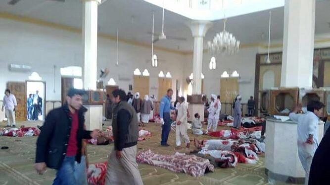 Varias personas, junto a varios cuerpos sin vida en la mezquita atacada en Egipto