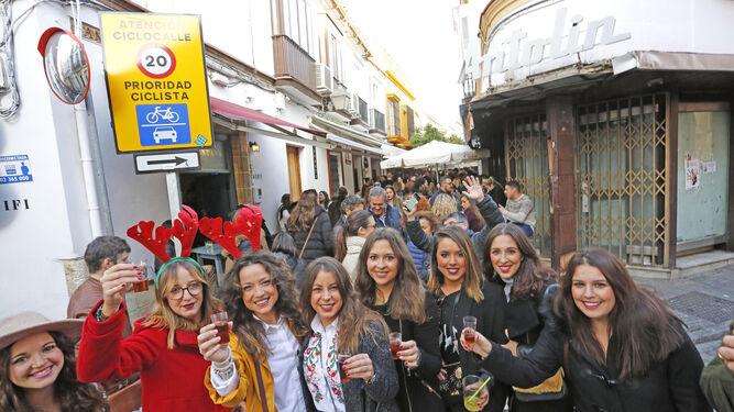 Un grupo de jóvenes brindan con la calle San Pablo a rebosar de fondo.
