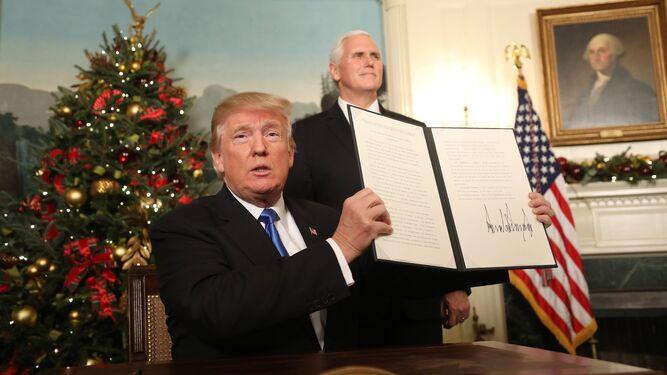 Donald Trump firma su proclamación en la sala de recepciones diplomáticas de la Casa Blanca ante el vicepresidente, Mike Pence, ayer en Washington.