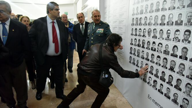 La familiar de una de las víctimas toca su foto durante la inauguración de la muestra.