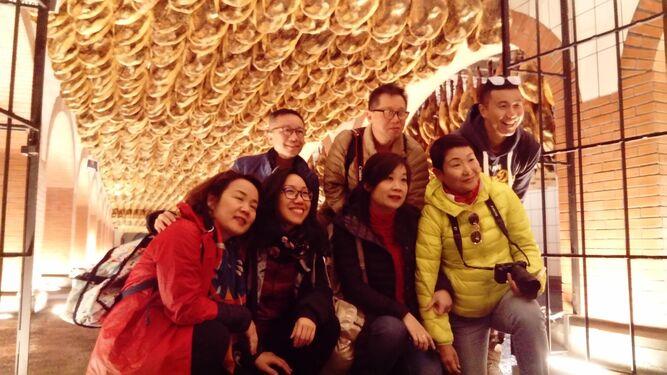 Los periodistas asiáticos, en una de las salas de curación de Cinco Jotas y en una sesión de corte.