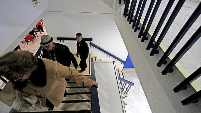 Varios usuarios de las instalaciones, subiendo ayer por la tarde las escaleras hacia la primera planta.
