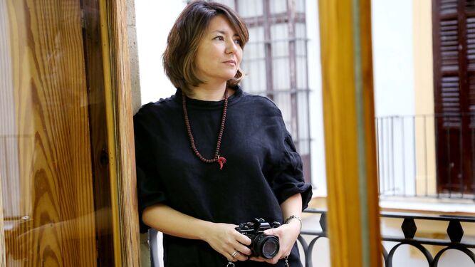 Arriba, la fotógrafa María Higuero, en una imagen tomada por Vanesa Lobo; a su lado, las manos del tonelero que parece bailar con la bota.