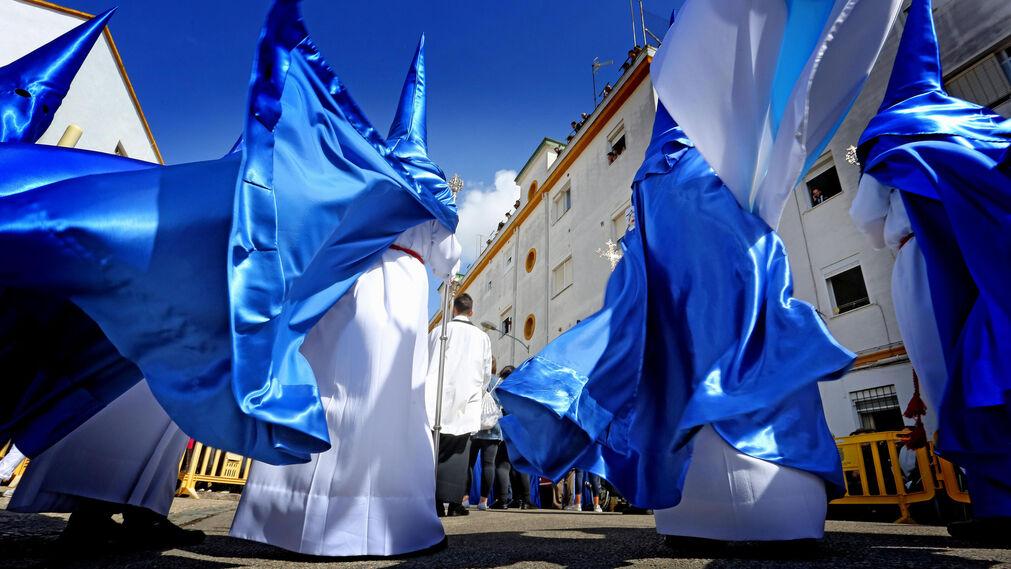 Hermanos de la Exaltación avanzan por la barriada de La Vid mientras el viento azota sus túnicas.