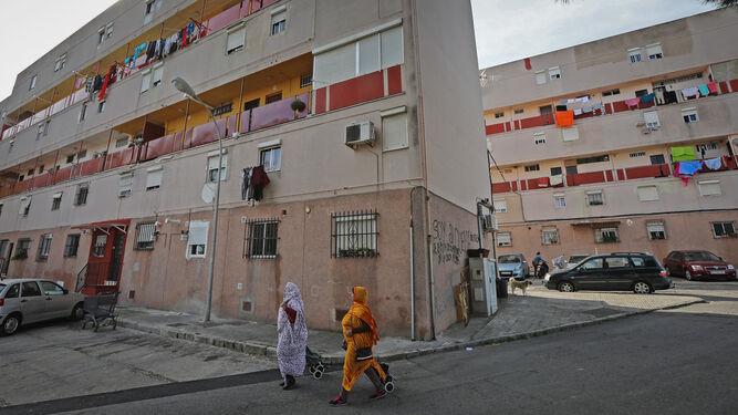 Dos mujeres pasan ayer por la mañana ante uno de los bloques de la barriada de San Juan de Dios.