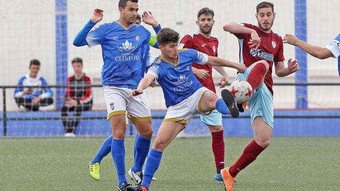 Javi Gómez y Antonio Sánchez estiran la pierna para llegar al balón.