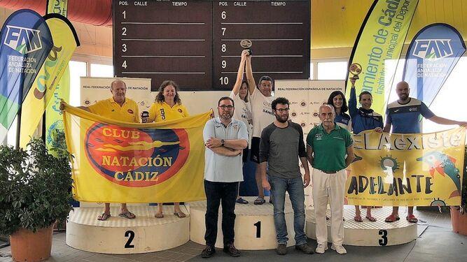 Manuel Mestre y Lola Polonio levantan la copa de campeones de la clasificación general absoluta.