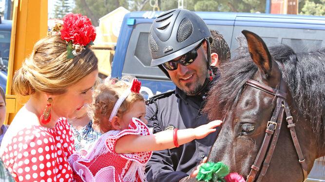 Una madre y su hija acarician un caballo de la Policía Nacional en el Real.