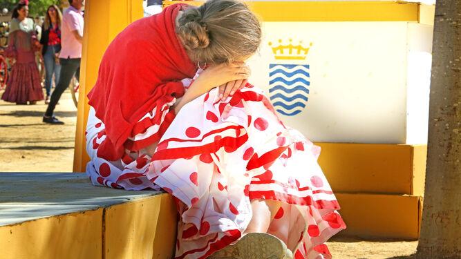 Una joven apoya su cabeza en sus rodillas en un signo de cansancio.