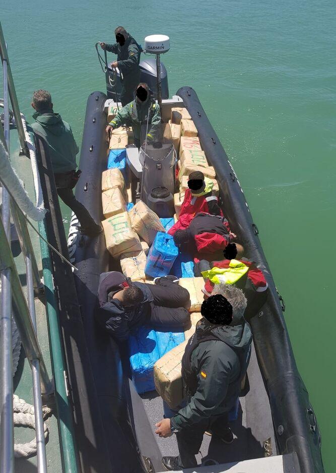 La semirrígida interceptada por la Guardia Civil, con la droga y los detenidos.